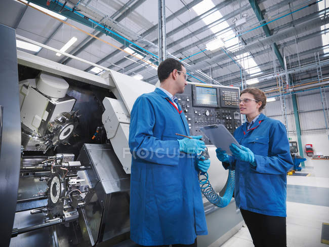 Engineers with machinery in factory — Stock Photo