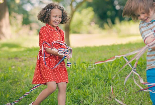 Niños jugando con cintas al aire libre - foto de stock