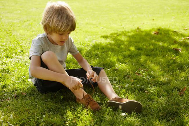 Garçon attacher sa chaussure dans l'herbe — Photo de stock