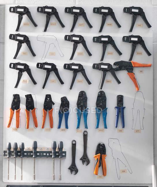 Outils disposés et organisé sur mur blanc — Photo de stock