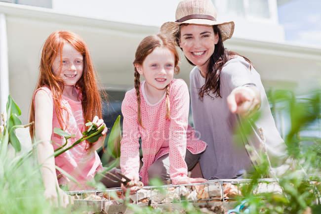 Madre e hijas jardinería - foto de stock