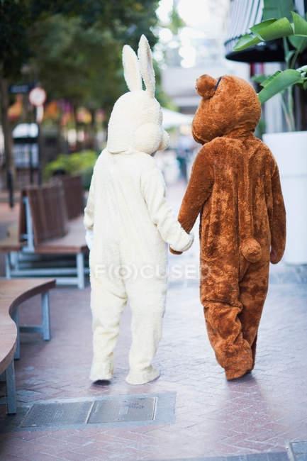 Menschen in Hasen- und Bärenkostümen auf der Straße — Stockfoto