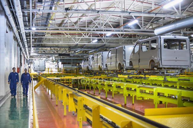 Робітники, що йдуть поряд з транспортними засобами в автомобільній фабриці — стокове фото