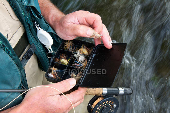 Fly fisherman holding fly box in river — Stock Photo