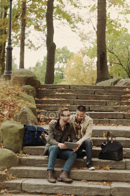 Гей пара с помощью цифрового планшета на ступеньках — стоковое фото