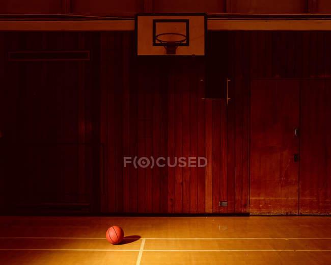 Cancha de baloncesto vacía con la bola en el piso - foto de stock