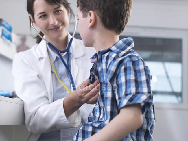 Médico verificando respiração do menino com estetoscópio — Fotografia de Stock