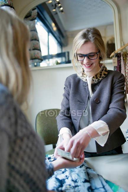 Sales assistant giving change to customer — Stock Photo