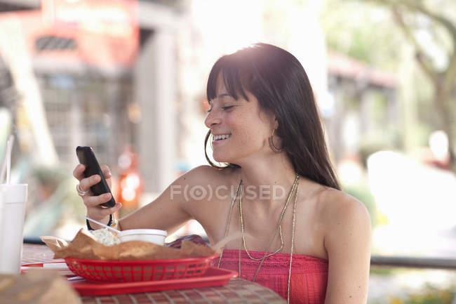 Mujer joven sosteniendo el teléfono móvil en la cafetería al aire libre, sonriendo - foto de stock