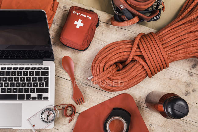 Top view of climbing equipment packing with red first aid kit, climbing ropes and laptop — Stock Photo