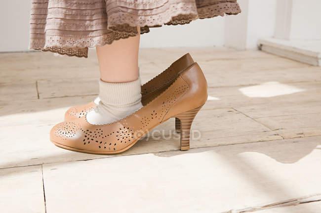 Immagine ritagliata di ragazza che indossa scarpe di grandi dimensioni — Foto stock