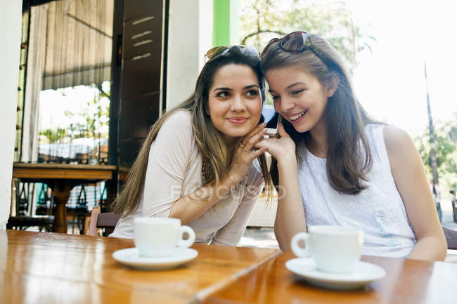 Female friends listening to cellphone together — Stock Photo