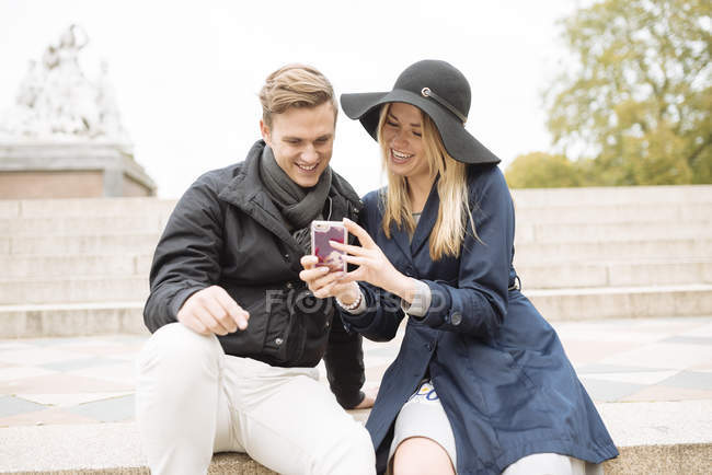 Young couple sitting on step reading smartphone texts, London, England, UK — Stock Photo
