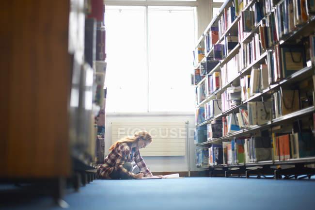 Jovem estudante universitário do sexo feminino trabalhando no chão da biblioteca — Fotografia de Stock