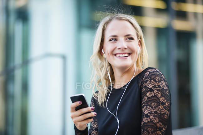 Junge Frau, die Auswahl der Musik auf Smartphone in Stadt — Stockfoto