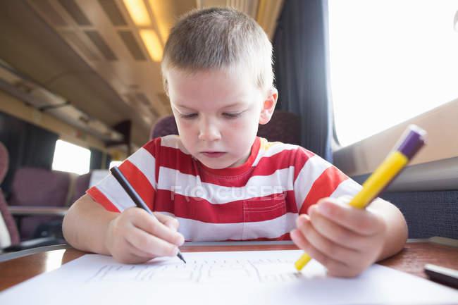 Young boy drawing in train — Stock Photo