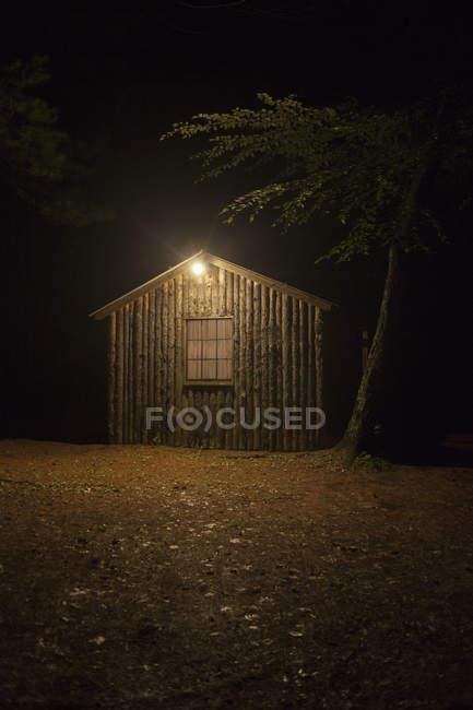 Capannone in legno illuminato con luce elettrica di notte — Foto stock