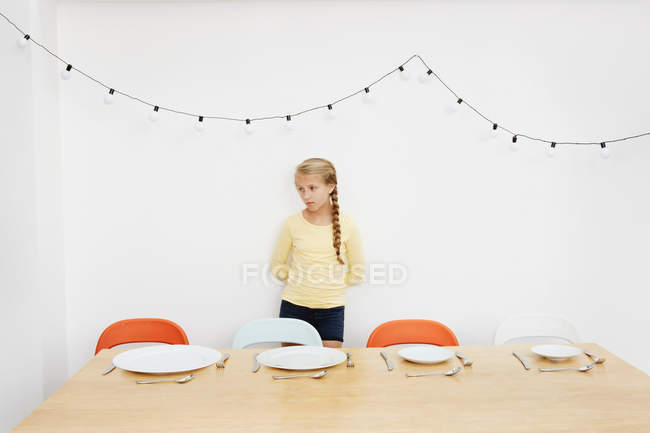 Girl waiting by table with empty plates — Stock Photo