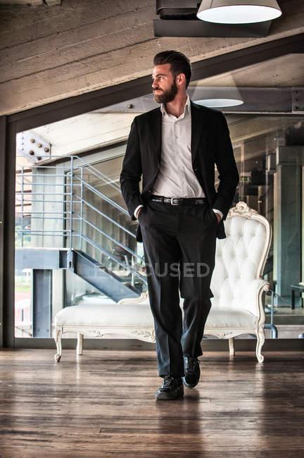 Попередній вигляд дорослого чоловіка в костюмі руки в кишенях, дивлячись на — стокове фото