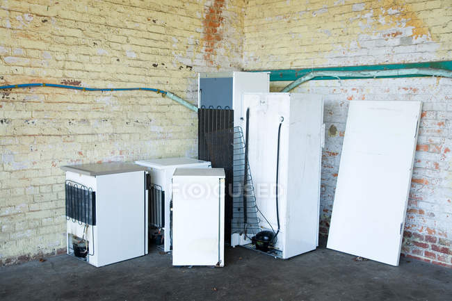 Discarded fridges and freezers placed near wall — Stock Photo