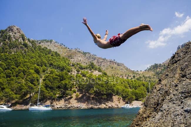 Junger Mann taucht ins Meer, Cala Tuent, Mallorca, Spanien — Stockfoto