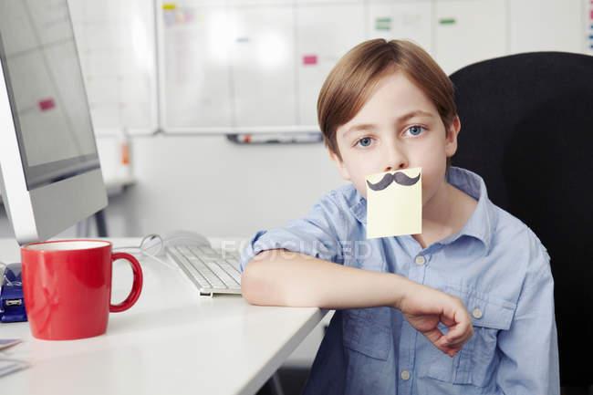 Menino com nota adesiva cobrindo a boca, desenho de bigode — Fotografia de Stock
