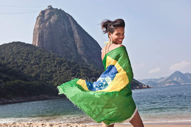 Man on beach with Brazilian flag, Rio de Janeiro, Brazil — Stock Photo