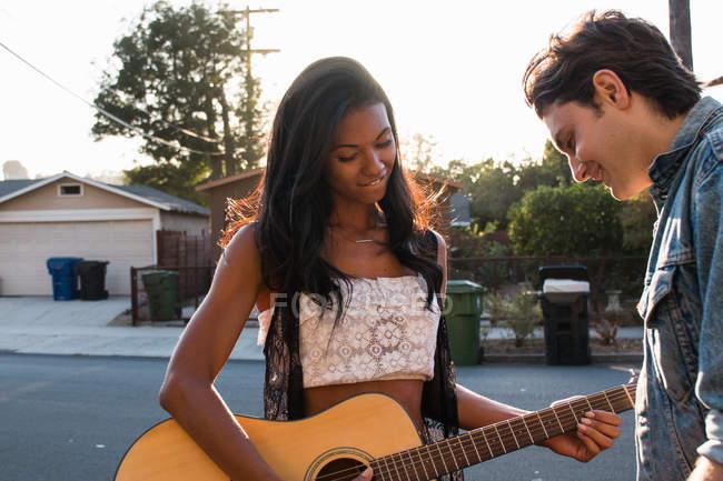 Jeune couple à l'extérieur, jeune femme jouant de la guitare — Photo de stock