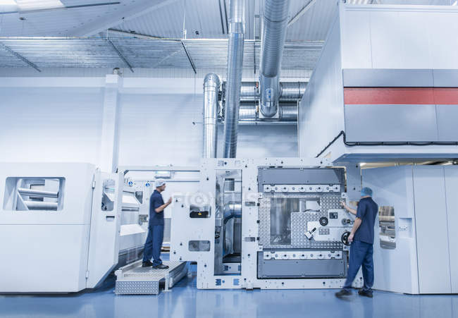 Workers operating machine in food packaging printing factory — Stock Photo