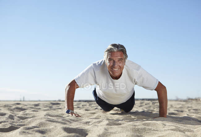 Uomo anziano che fa flessioni sulla spiaggia — Foto stock