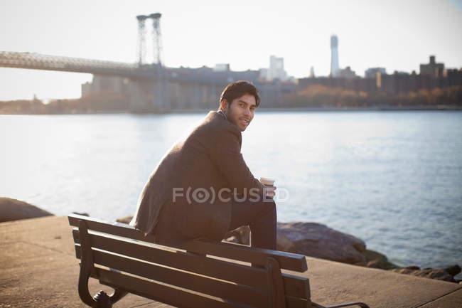 Smiling man sitting on park bench — Stock Photo