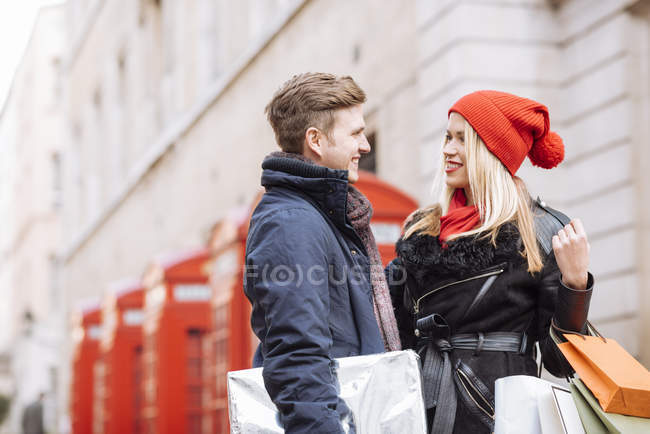 Young shopping couple and red phone boxes, London, UK — Stock Photo