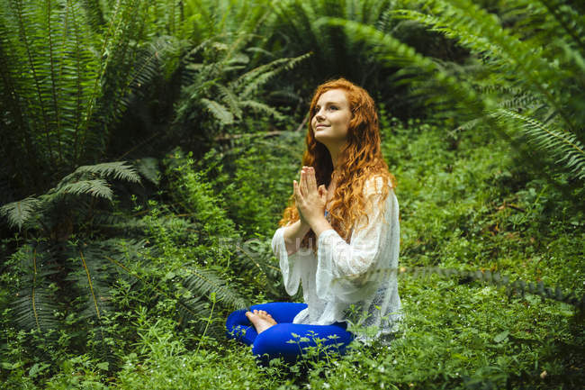 Young woman in forest practicing yoga in lotus position — Stock Photo
