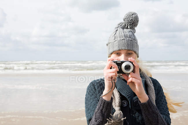 Woman by the sea with camera — Stock Photo