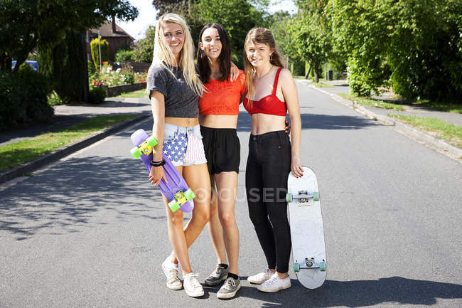 Portrait of three young women with skateboards — Stock Photo