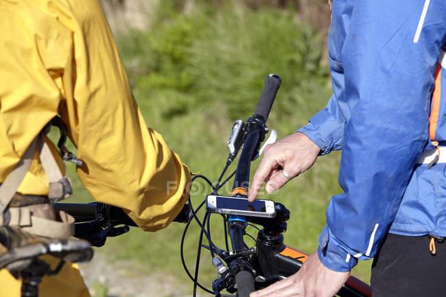 Обрезанное мнение велосипедистов с помощью смартфона, придает велосипедов — стоковое фото