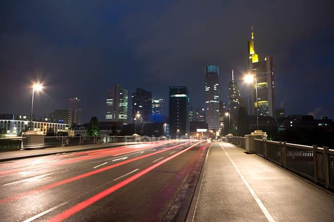 Arranha-céus cidade de Frankfurt com trilhas leves na estrada — Fotografia de Stock