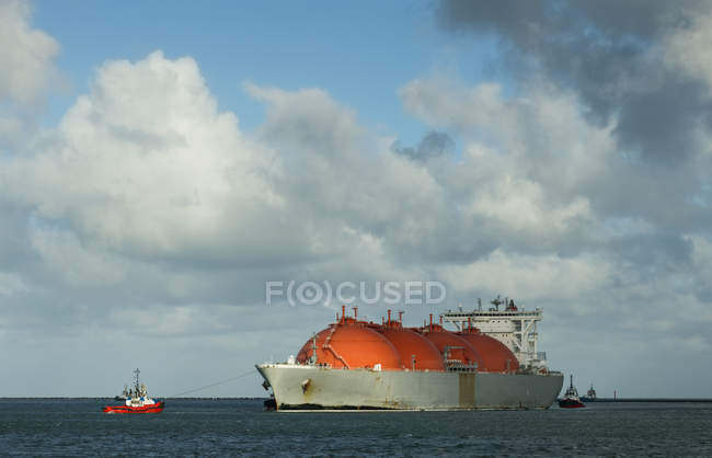 Gas tanker entering harbour with help of tug boat — Stock Photo
