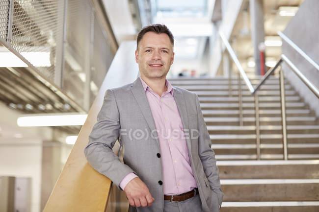 Ritratto di uomo d'affari in piedi su una scala d'ufficio — Foto stock