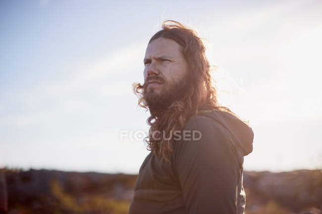 Portrait of man with long hair standing against blurred landscape — Stock Photo
