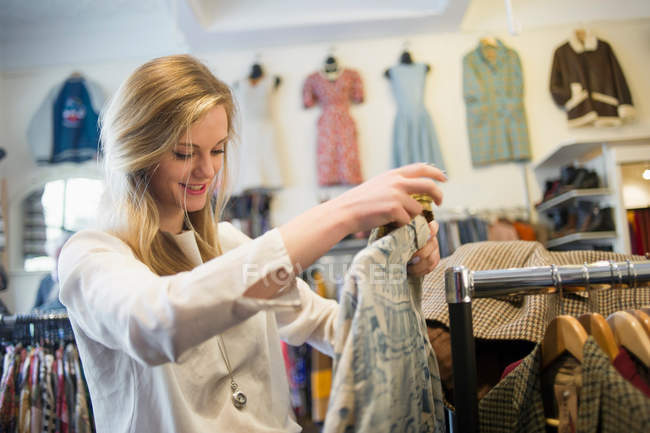 Young woman looking at top garment in shop — Stock Photo