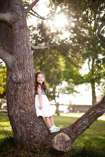 Портрет девушки, стоя на ствол дерева — стоковое фото