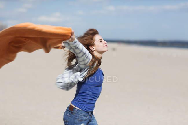 Jeune femme tenant la couverture sur la plage venteuse — Photo de stock