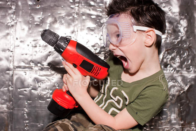 Boy with power tool and safety goggles — Stock Photo