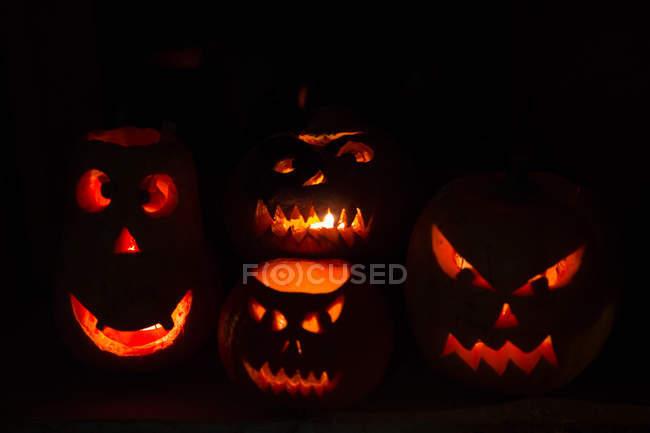 Illuminated pumpkin Jack O' Lanterns on black background, celebrations of Halloween — Stock Photo