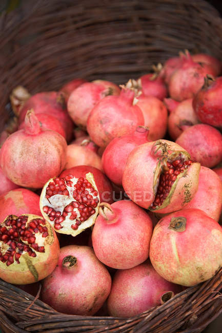 Pomegranates pile in basket at market stall — Stock Photo