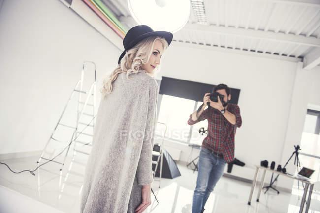 Male photographer photographing female model on studio white background — Stock Photo