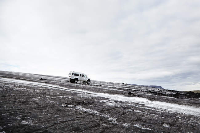 Four wheeled truck parked in icy black landscape, Iceland — Stock Photo