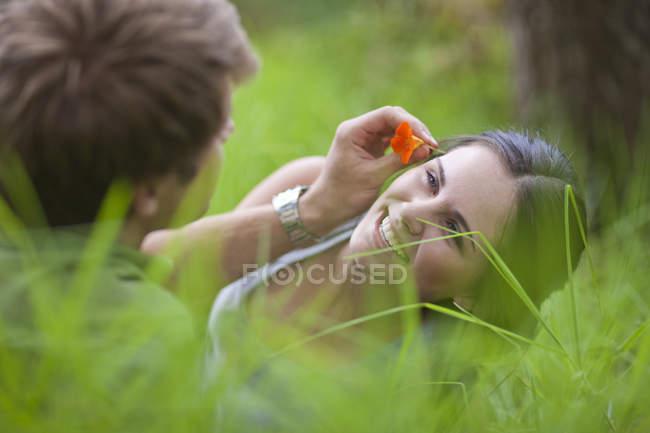 Jeune homme mettant la fleur dans le cheveu de femme — Photo de stock