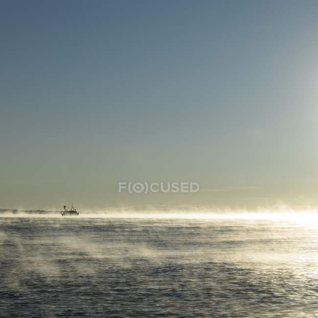 Seascape with fishing boat on horizon in dawn sunlit mist — Stock Photo